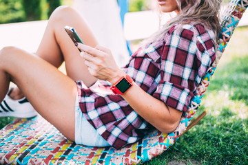 BUCHAREST, ROMANIA, - October 26, 2017: Person using smart watch and a smartphone walking on the park in a sunday. Woman making gestures on a wearable smart watch. Illustrative editorial content.