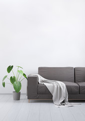 Modern vintage living room. Brown leather sofa on a grey wooden floor and light wall. 3D render.