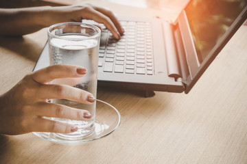 business woman drinking fresh water while working on computer laptop at office desk