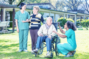 Asian and african nurses helping elder couple at rehab facility garden