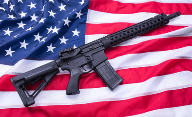 Custom built AR-15 carbine on American flag surface, background. Studio shot.