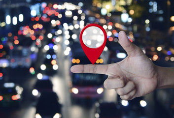 Map pin location button on finger over blurred colourful night light city with cars, Map pointer navigation concept