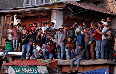 Photographers and onlookers take pictures of Fayaz Ahmad Hamaal, a suspected militant who according to local media was killed in a gun battle with Indian security forces, during his funeral in Srinagar