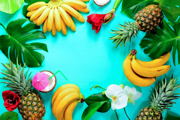Summer colorfull concept with tropical fruits and flowers, space for a text