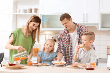 Parents and cute little children having breakfast with tasty toasted bread at table in kitchen