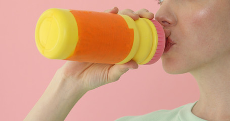 Sports woman drinks from fitness shaker at pink background