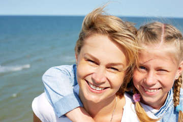 Happy mother and daughter laughing together outdoors. Close up