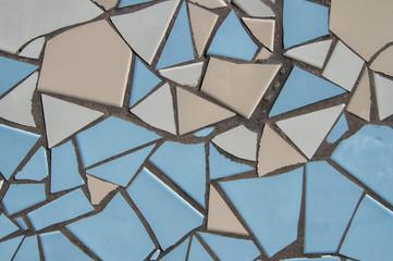 MOSAICO/ fondo con mosaico de azulejos partidos en color azul y beige en la fachada de un edificio.