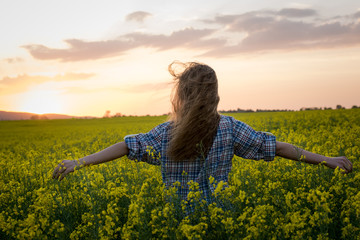 Garden Poster Culture Happy young woman in a field of canola seed in bloom. Freedom, nature, ecology and happiness concept.