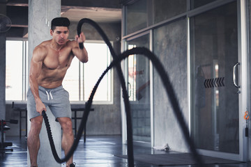 Fitness man with battle rope in gym