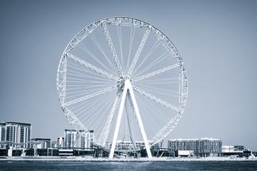 Ferris wheel in Dubai, United Arab Emirates, from blue sea. Seascape, skyline, urban landscape. Observation wheel, landmark, nonbuilding structure. Amusement, entertainment concept