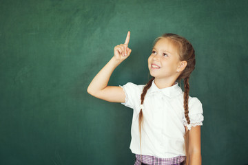 Smiling young little child girl in school on blackboard background. Education and school concept