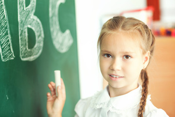 Young girl writing ABC on green chalkboard