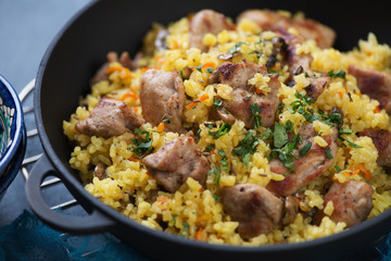 Close-up of pilaf with pork meat and mushrooms in a cast-iron pan, selective focus, horizontal shot
