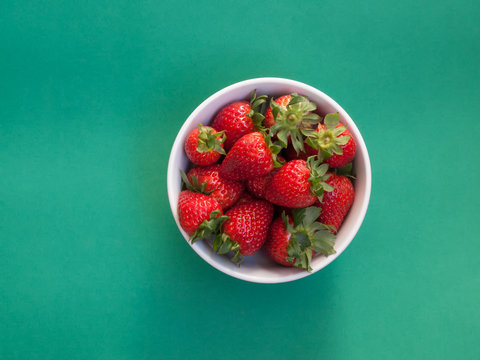Top view of strawberries on plain green background