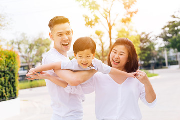 Asian family having fun and carrying a child in public park