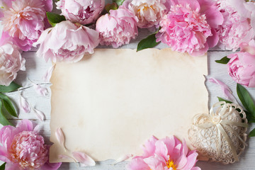 Pink peonies, lacy heart and paper for text congratulations, invitations on a wooden background