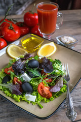 Salad diet for weight correction from the leaves of Lollo Rosso lettuce, watercress salad and other green herbs with tomatoes, olives and fitaki. Close up.