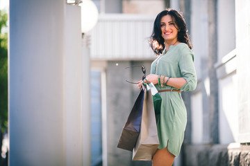brunette with a beautiful figure and smile is standing in summer tunic with packages and eyeglasses in her hands at day in the street