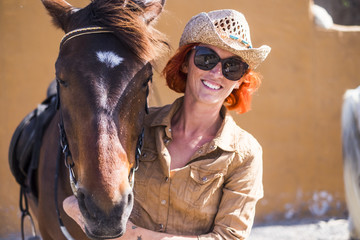 smiled beautiful girl red hair and cowboy hat with her best friend horse in friendship ready to live another adventure outdoor in leisure activity under the summer sun. alternative lifestyle