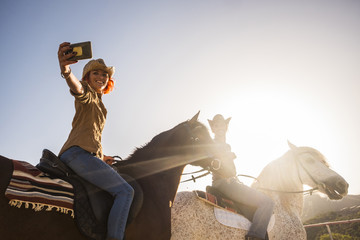 couple on horses riding outdoor under the sunlight in backlight for leisure activity taking selfie with modern mobile phone technology. alternative lifestyle concept for natural life with animal