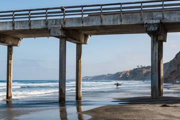 A lone male surfer carries a surfboard out to sea near a concrete pier in La Jolla, California