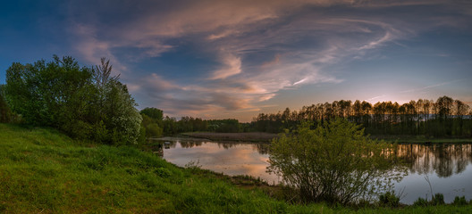 spring evening landscape after a sunset. a panoramic view from the high hilly coast of the river