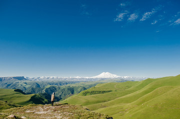 Landscape with a view of Elbrus and green meadows. A man looks alone at the snowy mountains.