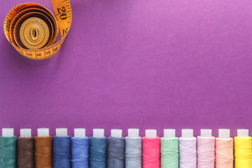 Many different colorful sewing threads and a measuring tape on a purple background