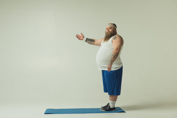 I chose my way. Full length portrait of calm fat man pointing arm sideways with confidence. He is standing on sporty mat. Copy space