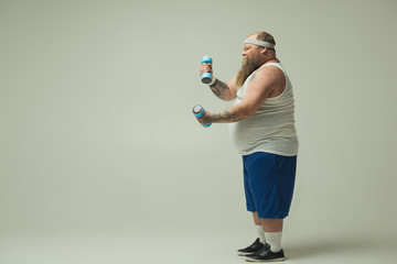 Profile of constrained obese bearded guy having intensive training. He is standing and trying to raise weights. Copy space