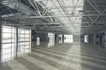Interior of huge bright empty building inside with high ceiling and wide windows