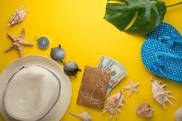 A woman's hat with round sunglasses and seashells, and money with a passport on a yellow background. Top view with a place for inscription or advertising