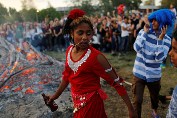 A Roma girl walks around a bonfire during the annual Kakava spring festival in Edirne