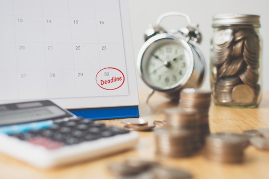 Tax payment season and finance debt collection deadline concept. Money coins stack, calendar, calculator and clock