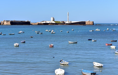 Small boats in the bay of the city beach La Caleta in Cadiz, Andalucia Spain