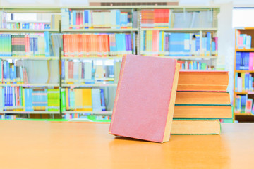 old book red - green. heap are interior library school on wooden table and blurry bookshelves background. education learning concept with copy space add text
