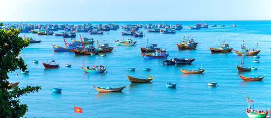 Mui Ne, Vietnam - April 22, 2018: Fishing village and traditional fishing boat with hundreds boats anchored in beautiful stream. This is  bay for boats avoid rainy season storms in Mui Ne, Vietnam