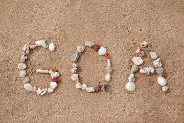 Text GOA made from shells on seashore
