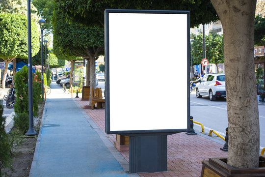 Blank vertical street billboard stand with city background.