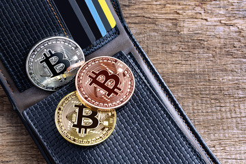 Bitcoins placed into leather wallet on the wooden table. Virtual money or cryptocurrency concept.