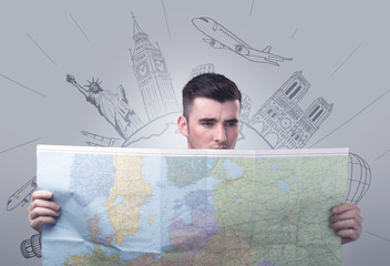 Handsome young man holding a map with famous sightseeing destinations above his head