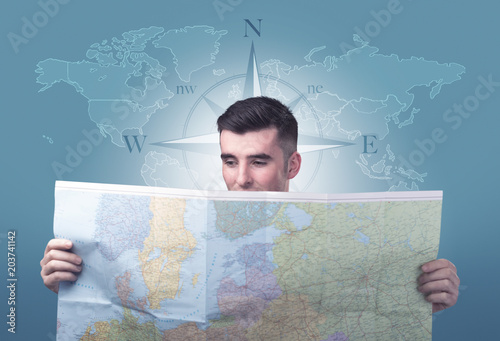 Handsome young man holding a map with a world map and a compass