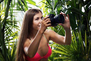 portrait of nice young woman is taking picture in the  jungle