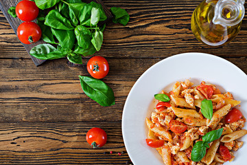 Penne pasta in tomato sauce with chicken, tomatoes, decorated with basil on a wooden table. Italian food. Pasta Bolognese. Top view. Flat lay