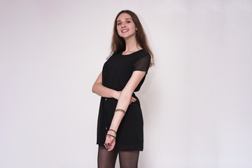 Portrait of a beautiful brunette girl on a gray background in a dress.