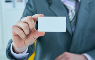 Businessman in grey suit and a pink shirt shows business card with copy space, shallow dept of field.