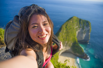 young beautiful and happy Asian Korean tourist woman taking selfie picture smiling carrying backpack after hiking excursion on top of tropical sea cliff