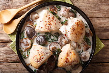 Pieces of chicken with wild mushrooms and spinach in a creamy sauce close-up on a table. horizontal top view