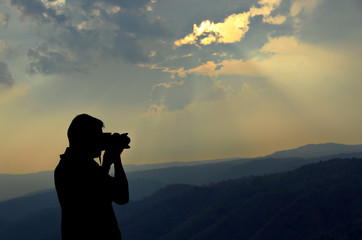 The photographer silhouette with mountain background.